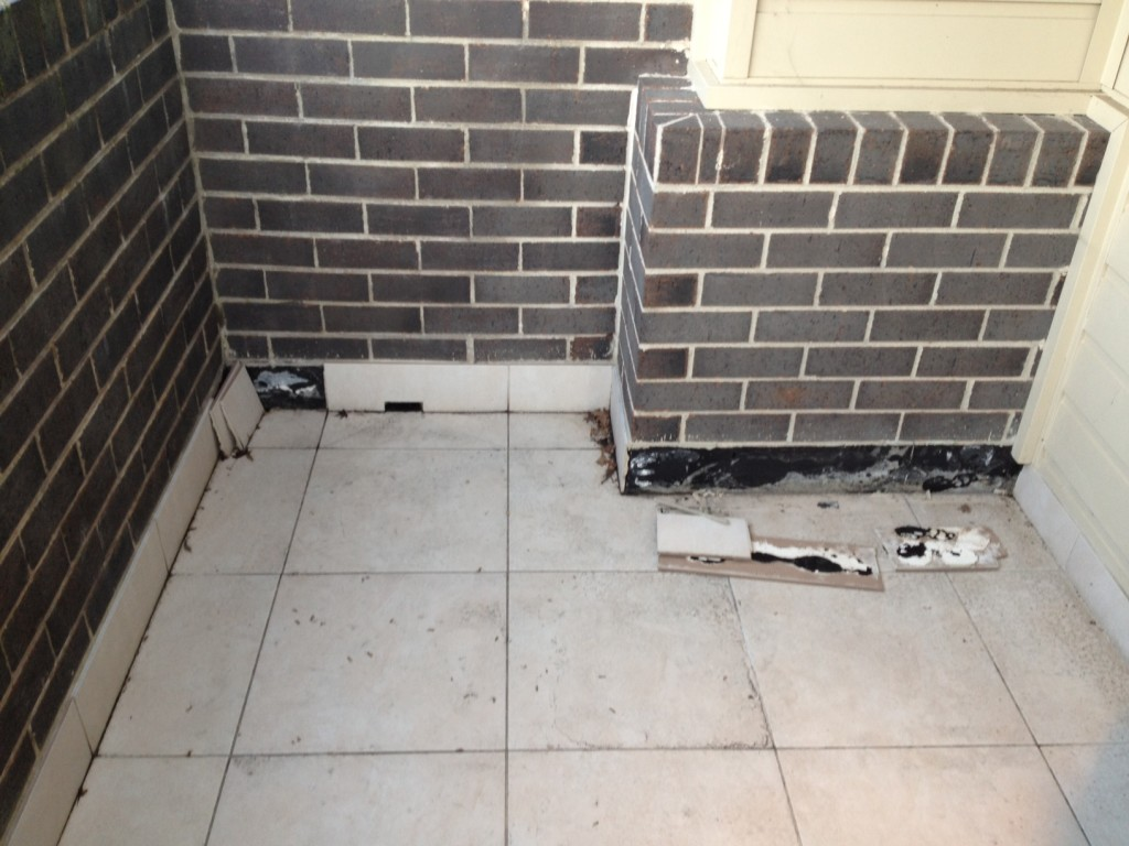 Failed membrane and tile adhesive which was rectified prior to epoxy regrouting to reseal and waterproof this balcony.