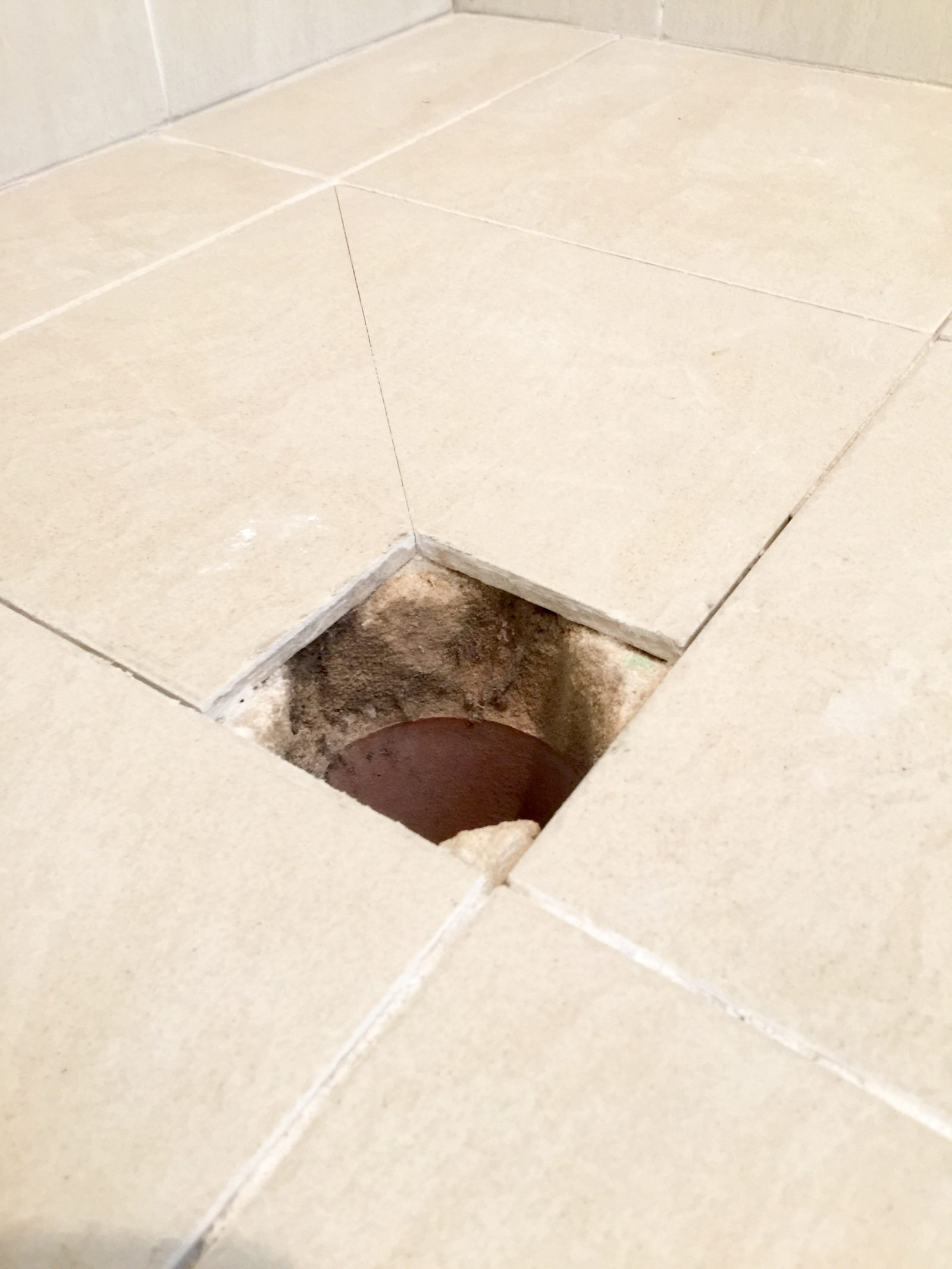 Floor waste removed showing exposed sand and cement screed which gets saturated from shower water
